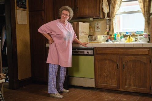 Actress Amy Adams wears a pink oversized t-shirt and leans against a kitchen countertop.