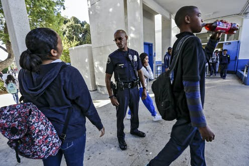 An African American police officer looks at two African American students a school.