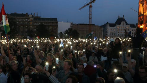 A crowd of white people holding candles in the dark.