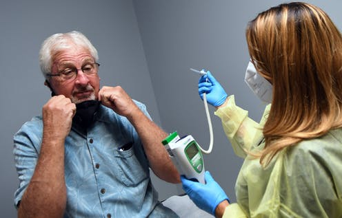 Tony Potts, a 69-year-old retiree, removes his face mask for a temperature check just before receiving his first injection in a Phase 3 COVID-19 vaccine clinical trial sponsored by Moderna.