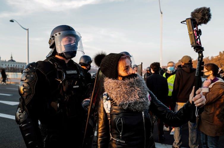 Une femme filme un garde mobile lors de la manifestation pour la Marche des libertés du 27novembre à Paris