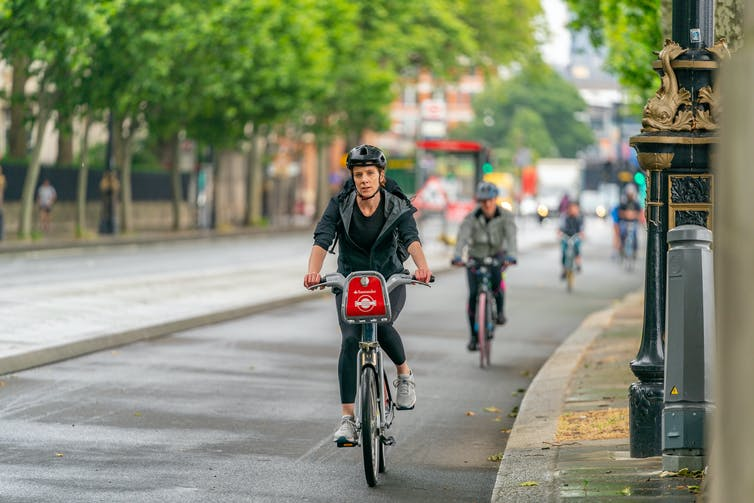 Cyclists riding down a tree-lined path in a city.