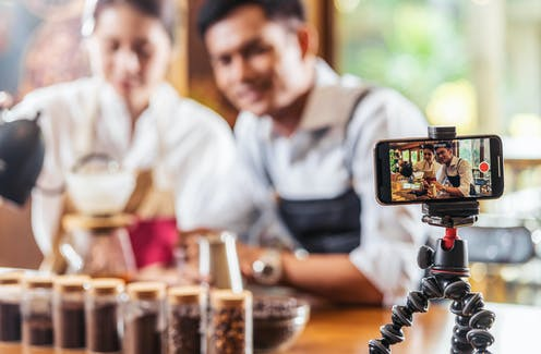 Man and woman record themselves making coffee on a smartphone.