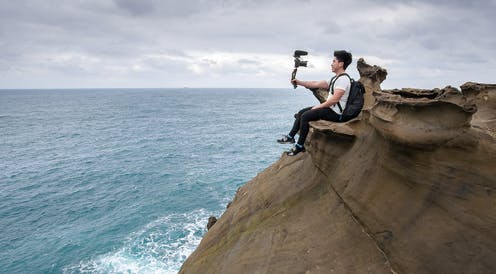 Man sitting on a rock ledge taking a selfie, next to the ocean