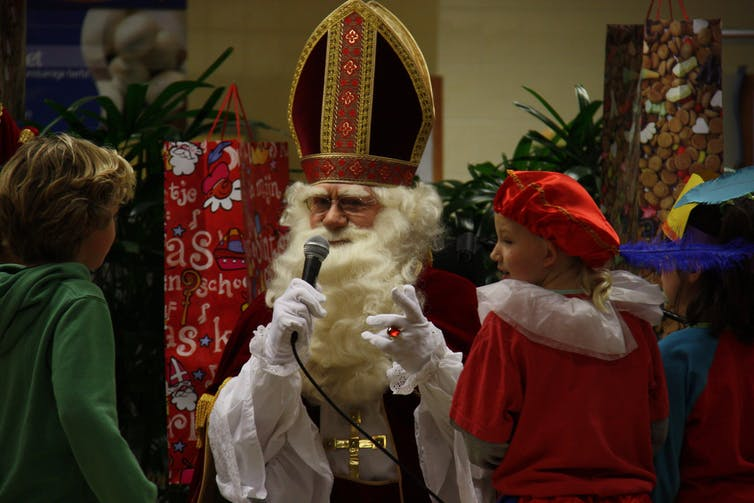 Sinterklaas has a white beard and is dressed in a red jacket, speaking with some children.