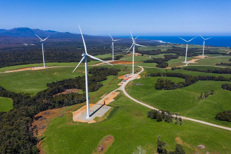 Aerial view of win turbines over a green field.