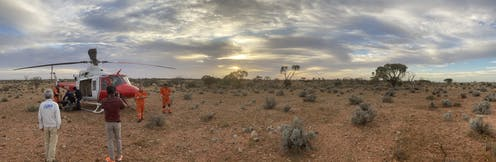 Several people and a helicopter in an outback Australian landscape.