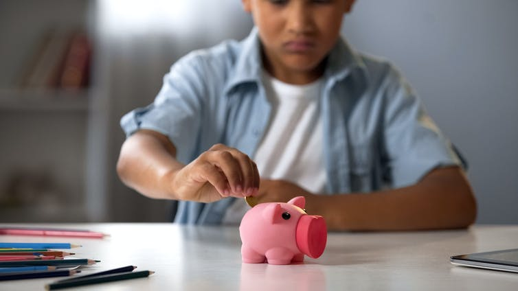 Boy putting a coin into piggy bank.