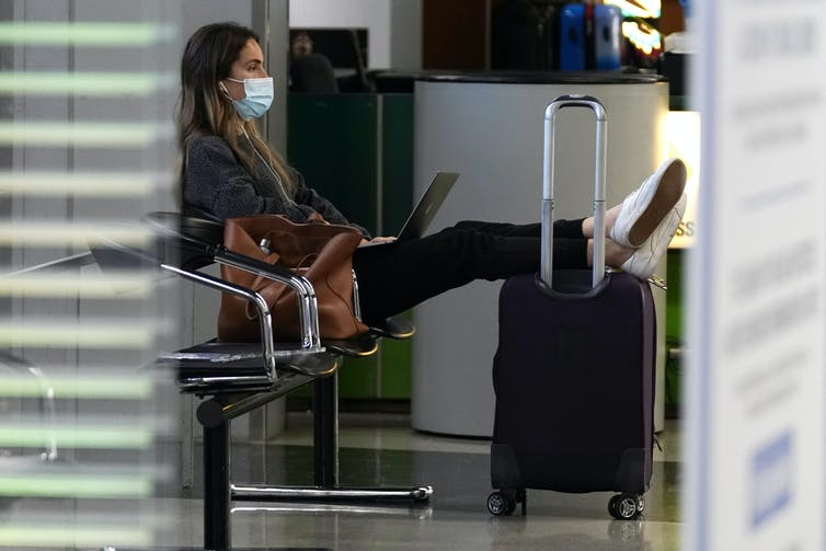 A young woman sits in an airport, wearing a mask.