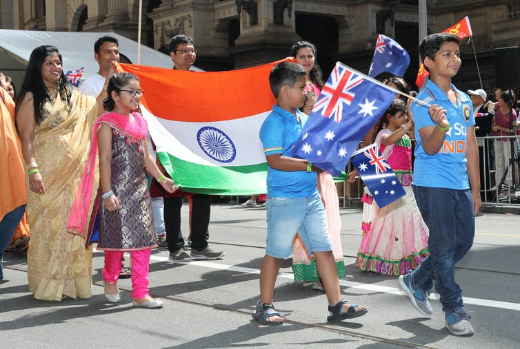 Family waves Indian and Australian flags in an Australia Day parade.