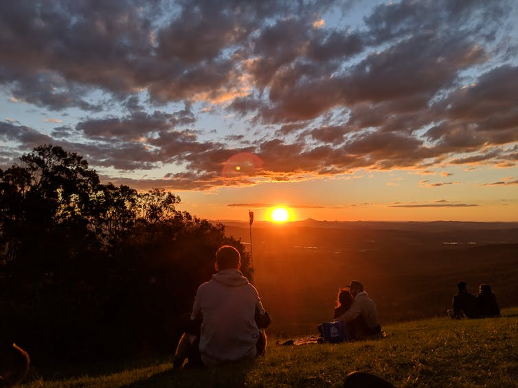 People sitting on a hill are watching a sunset in the distance.