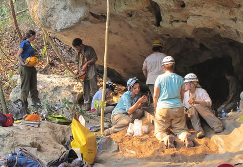 archaeologists excavate at the mouth of a cave