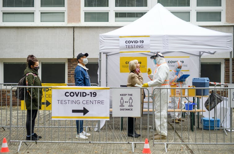 Three people queue outside a white gazebo to get a COVID-19 test.