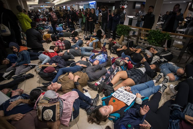 Dozens of young people lie on the floor of a food court.