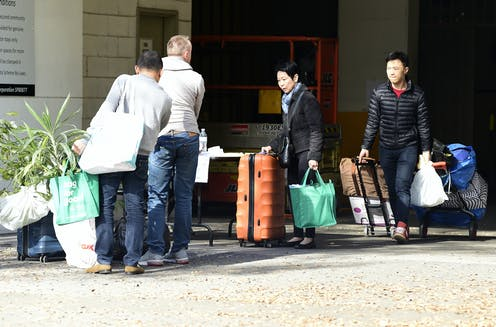 Evacuated residents leave the Mascot Towers apartments with their belongings