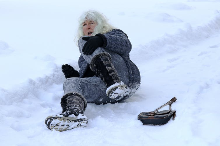 A woman lies on snowy ground after slipping.