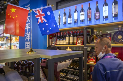 A visitor wearing a face mask to protect against the coronavirus looks at a display of Australian wines at the China International Import Expo (CIIE) in Shanghai