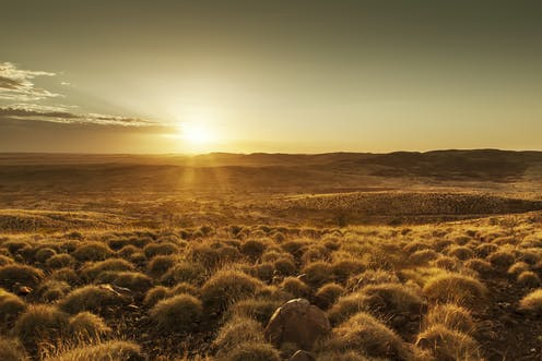 A sunset over an arid landscape in the Australian outback.
