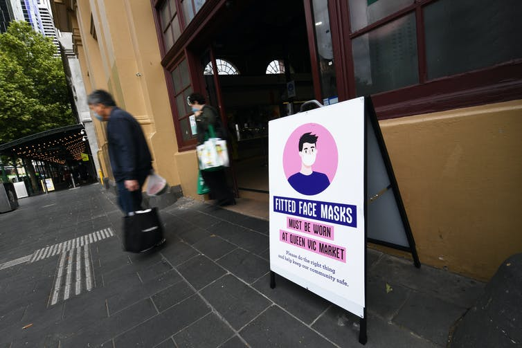 A sign in Victoria outside Queen Victoria market noting face masks are compulsory.