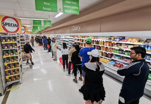 Shoppers lined up in a supermarket aisle
