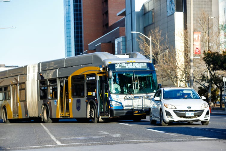 photograph of a car and a bus driving