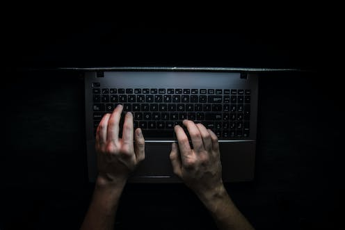 Two hands on a laptop keyboard, surrounded by darkness