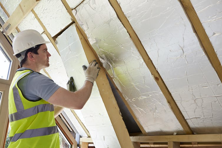 A builder installs insulating boards into the roof of a house.