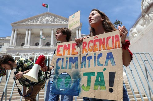 Children hold sign saying 'emercencia climatica ja!' in front of building flying a Portuguese flag