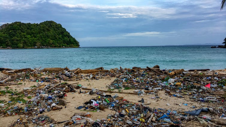 A tropical beach strewn with plastic waste.