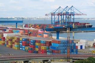 Coloridos contenedores de transporte y grúas llenan un bullicioso puerto marítimo.
