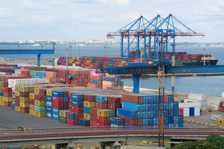Colourful shipping containers and cranes fill a bustling seaport.