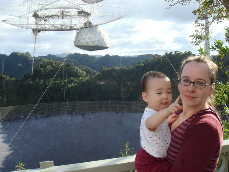 Woman and baby daughter stand in front of radio telescope.