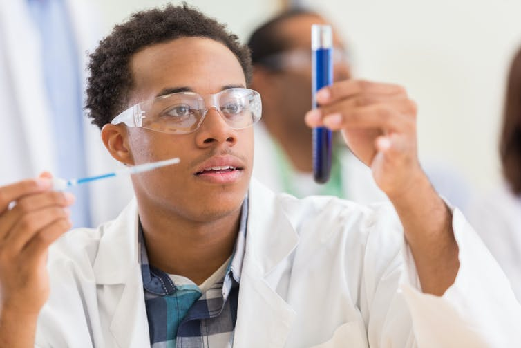An African American male scientist is looking at a test tube in a lab.