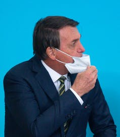 Bolsonaro adjusts his mask