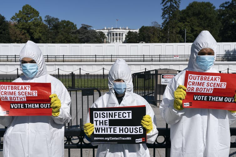 Protesters wearning personal protective equipment hold signs reading Disinfect the White House and Vote Them Out, with the White House in the background, in October 2020.