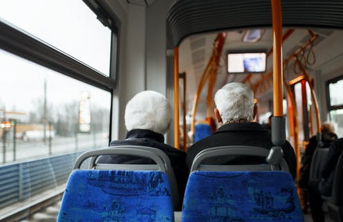 The back of the heads of two elderly passengers seated on a bus