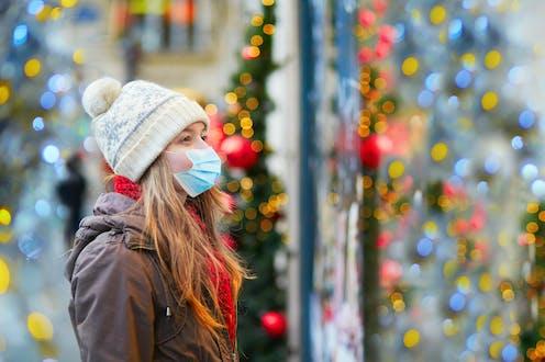 Una niñas con mascarilla y gorro de lana mira un escaparate con ambiente navideño.