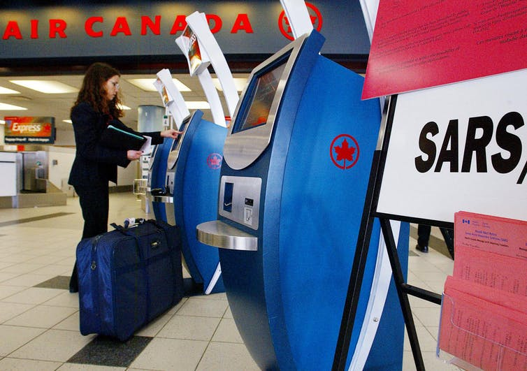 A woman in a black suit with a blue suitcase uses an Air Canada check-in kiosk at the airport. A sign with the text SARS is in the foreground.