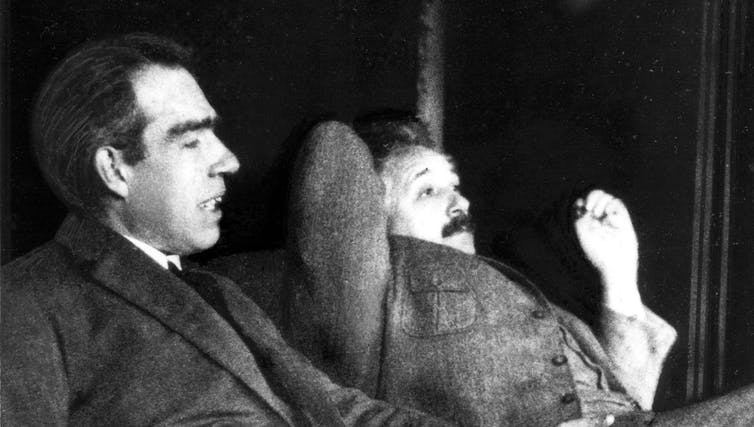 Black and white photo of Niels Bohr and Albert Einstein sitting next to each other looking pensive.