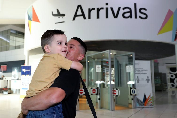 A man embraces a young boy at the arrivals hall in Perth airport.