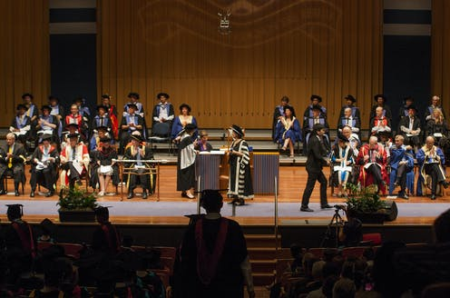 university leaders on stage during graduation ceremony