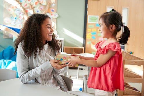 Girl giving gift to kindergarten teacher.