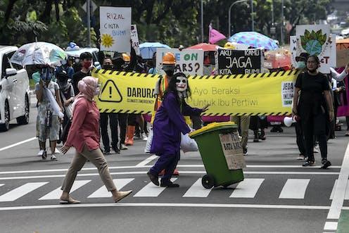 """Belasan anak muda dengan kostum membawa banner """"Jeda Untuk Iklim""""."""