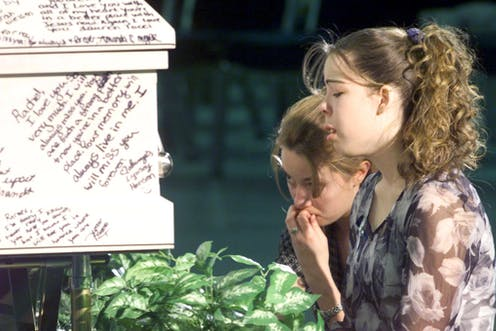 Two young women cry after writing messages on their friend's coffin after a mass shooting in Columbine High School, Littleton, Colorado.