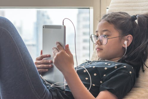 Girl looking at tablet with headphones in