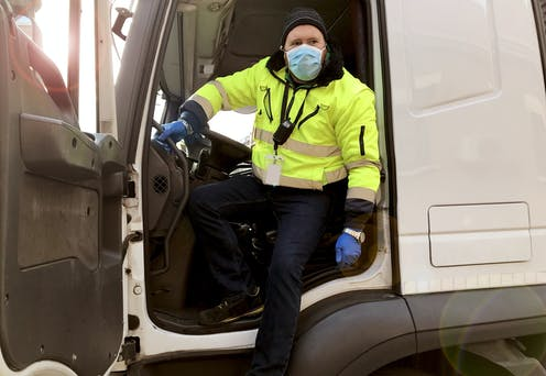 Truck driver stepping out of his cab, wearing a mask and gloves.
