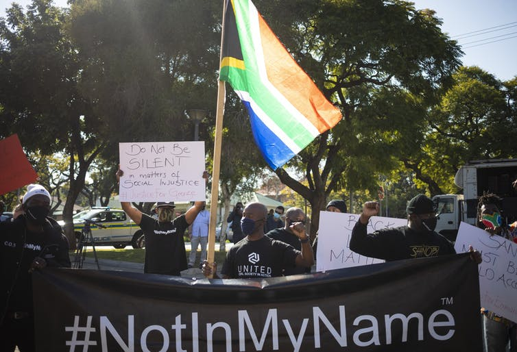 Protesters with a South African flag and Black Lives Matter banner at the US embassy in Pretoria,  South Africa, June 2020.
