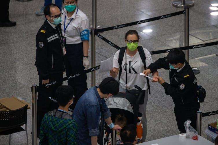 Officials at Hong Kong airport with travellers wearing masks.
