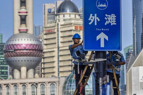 Two workers in hard hats install surveillance cameras on a signboard in the Shanghai Bund, August 2020.
