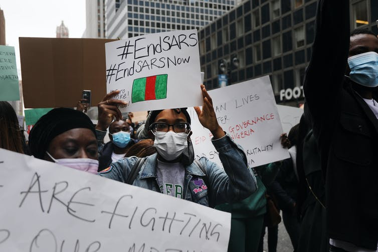 Crowd holding #EndSARS signs with New York skyscrapers visible in the background